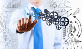 Activate working mechanism. Close up of businessman touching gears mechanism with finger Royalty Free Stock Image