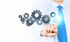 Activate working mechanism. Close up of businessman touching gears mechanism with finger Stock Image