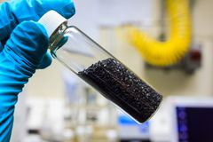 Activated carbon charcoal coconut. Activated carbon charcoal coconut in clear bottom for use in laboratory, holding by green medical rubber hand glove royalty free stock photography