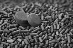 Activated carbon granules and tablets. Close up Royalty Free Stock Photos