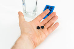 Activated carbon pills. Man`s hand holding activated carbon pills royalty free stock photography