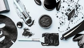 Activated Charcoal facial cosmetic setting with powder, Black head Mask, sheet mask and beauty tools accessories. Top view, flat lay. Modern beauty and skin stock photo