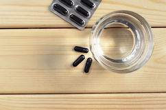 Activated charcoal and glass of water. Medical capsules with activated charcoal and glass of water on a wooden background, top view stock image