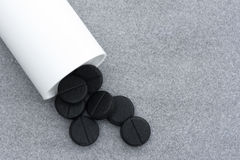 Activated Charcoal Tablets For cleansing the Body spilled From a Bottle On Gray Background Stock Images