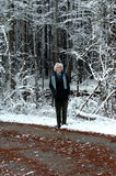 Active at 90. Elderly woman takes a walk down a quiet highway in the snow.  She is wearing a black leather jacket, patterned scarf and gloves Royalty Free Stock Images