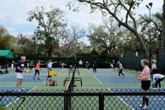 Active Adults Playing Pickleball Outdoors. Active adults and seniors on outdoor courts playing pickleball for fun, health and recreation stock images