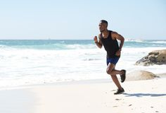 Active african american man running by water on the beach Royalty Free Stock Images