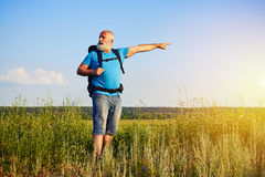 Active aged man with rucksack pointing at something in the field. Active aged man with white beard is standing in the field with rucksack and pointing at Stock Images
