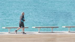 Active ageing of the elderly though the marina next to se beack. Outdoors running and sport workout against a blue sea. Empty copy space for Editor`s text stock photo