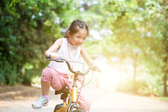 Active Asian child riding bike outdoor. Stock Images