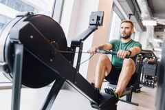 Active athlete man doing rowing workout. Active athlete man doing his rowing workout in a gym. Fit lifestyle stock images