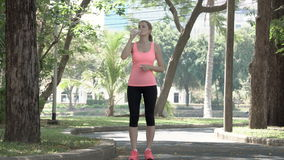 Active athletic young woman runner jogging in park. Fit female sport fitness training. Drinking water. Active athletic young woman runner with a ponytail jogging stock video footage