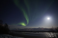 Active Aurora and Full Moon Light Over Cook Inlet Royalty Free Stock Photo