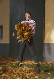 Active in autumn. Active woman collecting autumn leaves in the garden royalty free stock photo