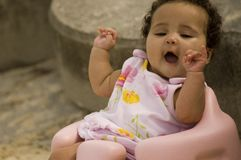 Active Baby. Portrait of an active baby girl sitting on a pink plastic chair.  Arms are upraised and mouth open Stock Image