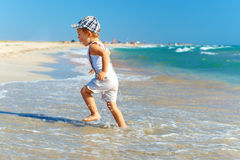 Active baby boy having fun in surf on the beach Royalty Free Stock Photography