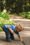 Active baby learning in nature. A little boy crouching down to pick up small stone Royalty Free Stock Photo