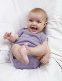 Active baby smiling and giggling. Playful baby playing with her legs Royalty Free Stock Images