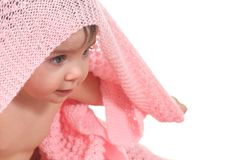 Active baby under a pink blanket. On a white isolated background Stock Photos