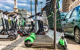 electric scooters parked in a row in avenida, lisbon in a beautiful day. date may 20 2019. modern electric scooters parked stock photos