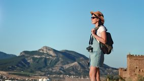 Active backpack travel woman standing on top of mountain admiring amazing landscape. Medium long shot. Smiling hiker young girl enjoying break having positive stock video footage