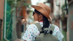 Active backpacker female tourist walking on narrow touristic city street steadicam establish shot