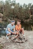 Active backpackers broiling some sausages near their camp fire living in tent. Broiling sausages. Active backpackers feeling satisfied while broiling some royalty free stock images