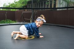 Active barefoot baby girl plays outdoors in playground. The little girl creeps on a trampoline Stock Photo