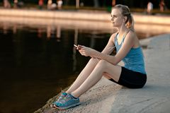 The girl in a t-shirt sitting near the water with a smartphone and headphones after jogging. Stock Photography
