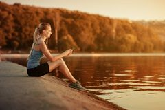 The girl in a t-shirt sitting near the water with a smartphone and headphones after jogging. Royalty Free Stock Photography