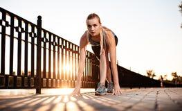 Athletic girl preparing to run Royalty Free Stock Image