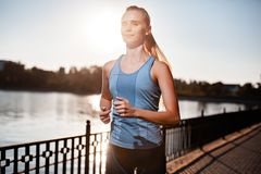 The girl in t-shirt is runnig around the lake. Stock Images