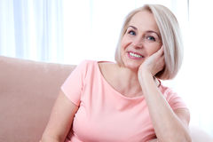 Active beautiful middle-aged woman smiling friendly and looking into the camera. Woman's face close up. Active beautiful middle-aged woman smiling friendly and stock image