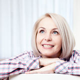 Active beautiful middle-aged woman smiling friendly and looking up at home in the living room. Woman's face close up. Active beautiful middle-aged woman smiling Stock Photos