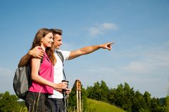 Active Beautiful young couple hiking ina nature climbing hill or Royalty Free Stock Photo