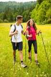 Active Beautiful young couple hiking ina nature climbing hill or Royalty Free Stock Images