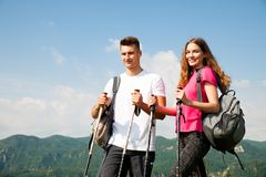 Active Beautiful young couple hiking ina nature climbing hill or Stock Photos