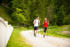 Active beautiful young couple hiking ina nature climbing hill or Stock Photography