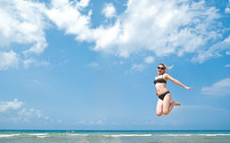Active beauty jumping. Young happiness woman is jumping against blue sky Stock Image