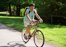 Active biking senior. Active senior riding a bike in a park in the summer with backpack Royalty Free Stock Photography