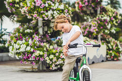 Active blond kid boy and bicycle near the sea. Toddler child dreaming and having fun on warm summer day. outdoors games for childr Stock Photography