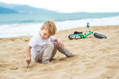Active blond kid boy and bicycle near the sea. Toddler child dreaming and having fun on warm summer day. outdoors games for childr Royalty Free Stock Image