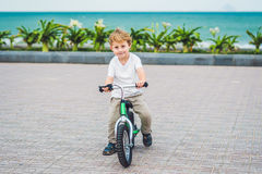 Active blond kid boy and bicycle near the sea. Toddler child dreaming and having fun on warm summer day. outdoors games for childr Royalty Free Stock Images