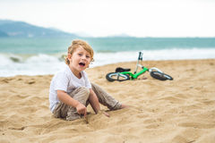 Active blond kid boy and bicycle near the sea. Toddler child dreaming and having fun on warm summer day. outdoors games for childr Stock Image