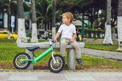 Active blond kid boy and bicycle near the sea. Toddler child dreaming and having fun on warm summer day. outdoors games for childr Royalty Free Stock Photography