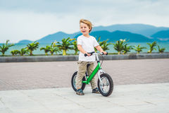 Active blond kid boy and bicycle near the sea. Toddler child dreaming and having fun on warm summer day. outdoors games for childr. Active blond kid boy driving Stock Photo