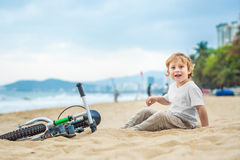 Active blond kid boy and bicycle near the sea. Toddler child dreaming and having fun on warm summer day. outdoors games for childr. Active blond kid boy driving Royalty Free Stock Images