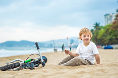 Active blond kid boy and bicycle near the sea. Toddler child dreaming and having fun on warm summer day. outdoors games for childr. Active blond kid boy driving Stock Images