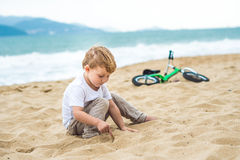 Active blond kid boy and bicycle near the sea. Toddler child dreaming and having fun on warm summer day. outdoors games for childr. Active blond kid boy driving Stock Photography