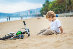 Active blond kid boy and bicycle near the sea. Toddler child dreaming and having fun on warm summer day. outdoors games for childr. Active blond kid boy driving Royalty Free Stock Image